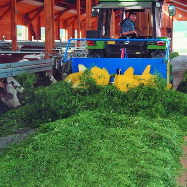 Farmer pushing feed with Agromatic RECK Silage Spreader.