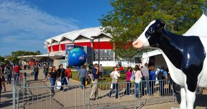World Dairy Expo 2018 coliseum globe with cow statue in foreground.